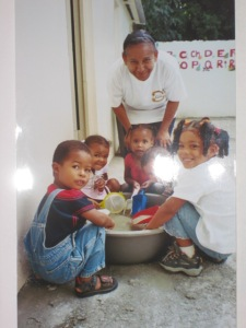 The first class of kids for the preschool program. They are playing in a small sandbox outside.